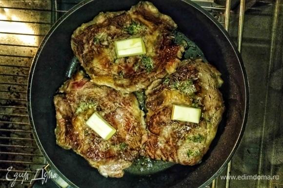 Сверху на каждый стейк положим по кусочку сливочного масла, накроем горячую сковороду фольгой и поставим в духовку на 7 минут.