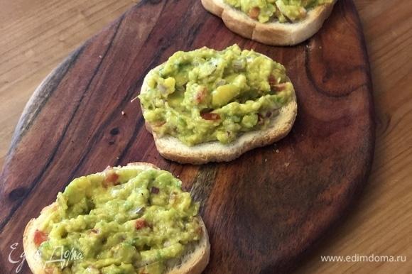 Начинаем собирать тосты. Выложите на хлеб массу из авокадо.