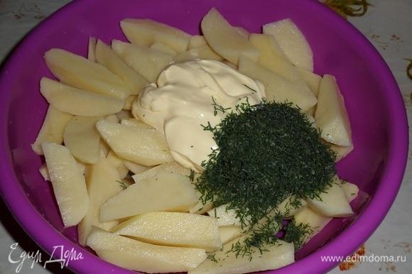 Картофель нарезаем дольками. Выкладываем в глубокую чашку нарезанный картофель, половину приготовленного майонеза и 1 ст. л. нарезанного укропа (я использовала замороженный укроп из собственных заготовок).