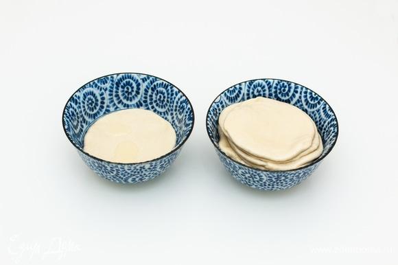 Подготовленные сочни по очереди сначала опустить в миску с растительным маслом, дать стечь лишнему маслу, а затем сложить все сочни стопочкой в свободную миску. Оставить сочни на 3–5 минут, чтобы они впитали масло, так легче будет растягивать.