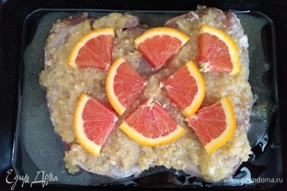Духовку разогреть до 220°C. Форму для запекания смазать маслом. Поместить индейку в форму вместе с маринадом. Апельсин нарезать на дольки и разложить сверху. Запекать птицу около 45–55 минут. Через 20 минут убавить жар и выпекать до готовности, периодически поливая выделившимся соком. Проверьте готовность с помощью термометра или проткнув ножом, вытекающий сок не должен быть красным.