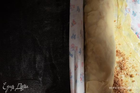 С помощью скатерти закрыть сначала узким краем, а потом постепенно свернуть рулетом, смазывая тесто маслом.