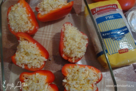 Перец разрезать пополам, очистить от семян. Наполнить рисом. Поставить в форму и добавить небольшое количество воды. Отправить в разогретую до 180°C духовку на 30 минут.