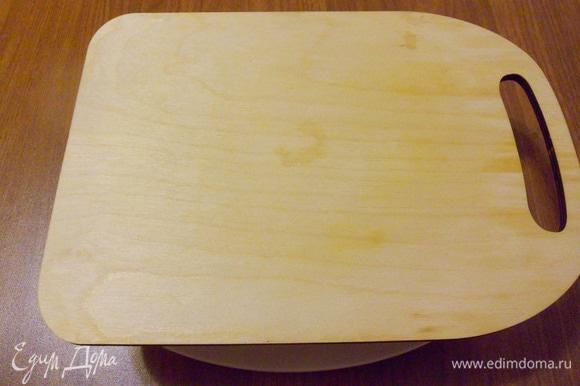 Перед покрытием кремом последнего коржа слегка прижать торт с помощью разделочной доски.