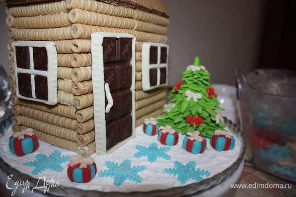 Двор посыплем сахарной пудрой (для имитации снега). Во дворе поставим елку и разместим другие фигурки из мастики.