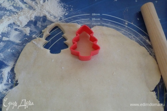 Далее раскатываем тесто в пласт толщиной 0,5 см. Формой для печенья вырезаем елочки.