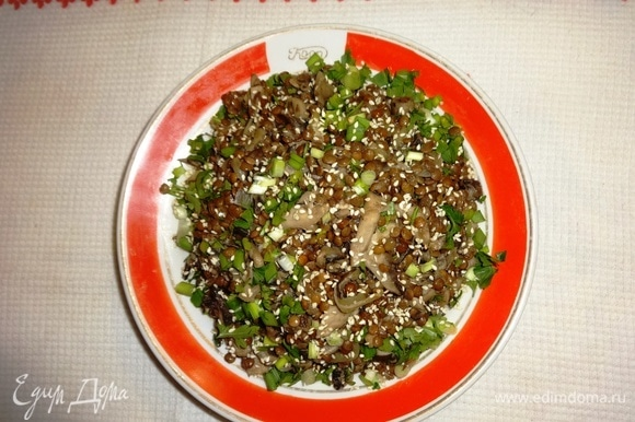 Выложить теплый салат из грибов и чечевицы на тарелку. Посыпать зеленью и обжаренным кунжутом.