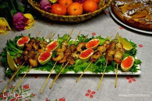 Большое блюдо украсить листьями салата, креветки на шпажках выложить на листья, рядом положить тарталетки, наполненные маскарпоне и красной икрой, и дольки лимона. Соком лимона сбрызнуть креветки. Вкусная праздничная закуска готова!
