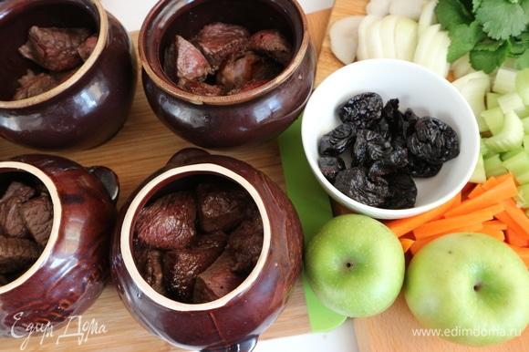Духовку разогреть до 180°C. Поместить мясо в горшочки. Жидкость со сковороды тоже отправить в горшочки. Из зеленых сортов яблок я отдала предпочтение сорту «Семеренко».