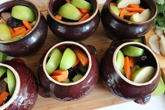 Положить в горшочки по 2 шт. чернослива без косточек, нарезанные стебли сельдерея, кусочки моркови, несколько яблочных долек (кожуру не чистить, семенную часть удалить).