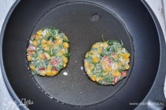 Разогреть на сковороде растительное масло и выкладывать тесто ложкой, формируя оладьи. Чтобы оладьи были ровные, я выкладываю тесто в силиконовые формочки для яичницы. Обжариваем оладьи 1–2 минуты с каждой стороны. Готовые оладьи выкладываем на салфетку, чтобы убрать излишки масла.