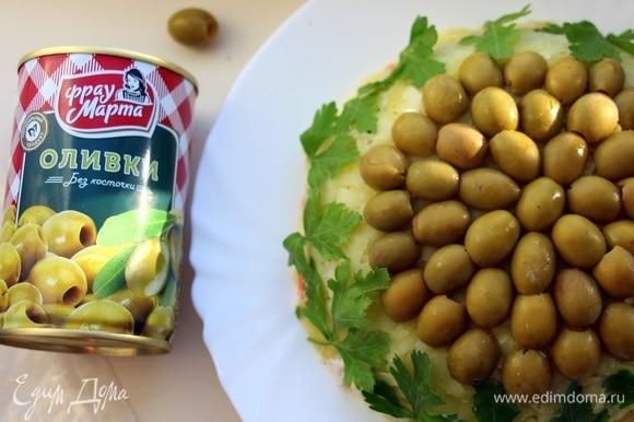 Далее аккуратно перевернуть салат на блюдо, снять пленку. Сверху украсить половинками оливок ТМ «Фрау Марта». Края салата украсить листиками петрушки.