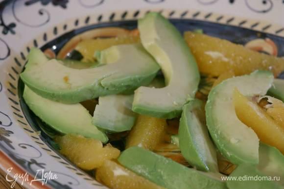 Авокадо почистить, удалить косточку, мякоть нарезать тонкими дольками и выложить к апельсину.