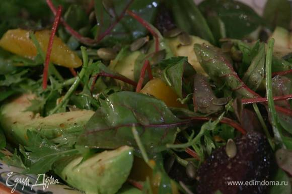 К апельсину с авокадо добавить чеснок, свеклу и салатные листья, полить все оливковым маслом, посолить, поперчить и перемешать, сверху посыпать подсушенными тыквенными семечками.