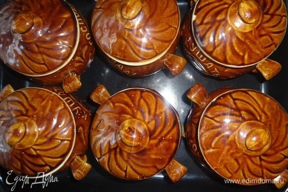В каждый горшочек положить по кусочку сливочного масла. Накрыть горшочки крышками, поставить на противень и поместить в холодную духовку. Разогреть ее до 180°C и с этого момента вести отсчет времени: готовить примерно 45–50 минут.