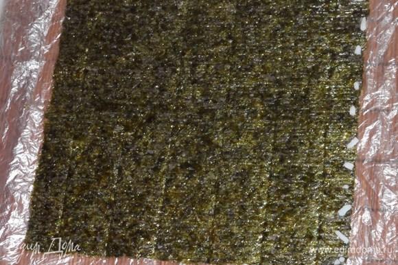 Циновку застелить целлофаном. Положить на него лист нори. С одного края положить несколько рисинок. Они нужны для крепкого скрепления.