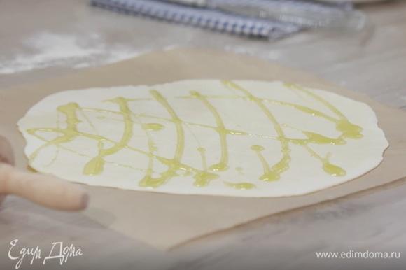 Переложить раскатанное тесто на бумагу для выпечки, сбрызнуть оливковым маслом.
