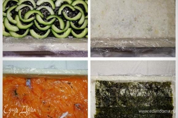 На лист нори укладываем огурец без сердцевины, слой риса, оставшуюся часть рыбы. На рыбу — оставшиеся рис и нори. Слегка придавливаем руками торт, чтобы он плотнее лег в форму.