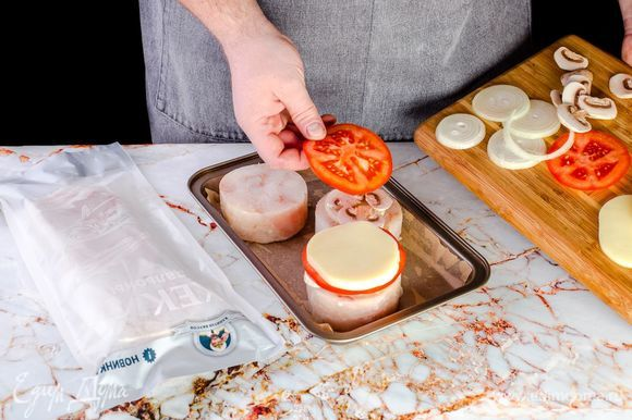 Разморозьте филе хека ТМ «Капитан Вкусов», посолите и поперчите. Застелите противень пергаментом, выложите рыбу, сверху – шампиньоны, лук, помидоры и моцареллу.