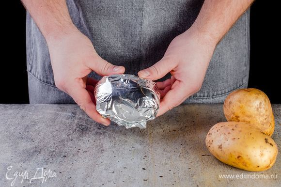 С помощью специальной щеточки хорошо промойте картофель. Не чистите. Оберните каждую картофелину в фольгу и запеките в духовке при 180°С в течение 50 минут до готовности. Ориентируйтесь по своей духовке.
