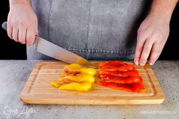 Когда перец приготовится, положите его в миску, накройте пищевой пленкой, чтобы он немного размяк. Очистите от кожуры нарежьте крупными полосками.