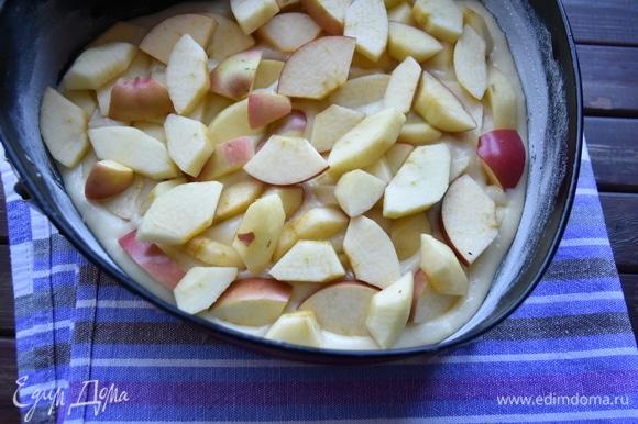 Форму для выпекания смазать маслом и слегка посыпать мукой. Остатки муки стряхнуть. Выложить половину теста. Сверху распределить нарезанные яблочные дольки.