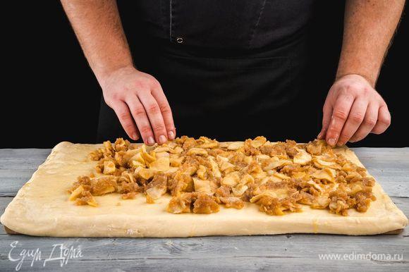 Из теста раскатайте прямоугольный пласт, выложите его на противень. Смажьте растопленным маслом и выложите начинку ровным слоем.