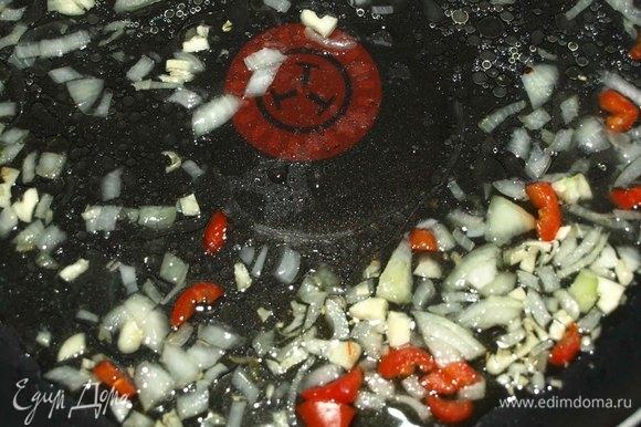 Лук, чеснок мелко нашинковать. Часть острого красного перца мелко нарезать. Перец лучше взять небольшой. Обжарить на разогретой с растительным маслом сковороде 1 минуту.