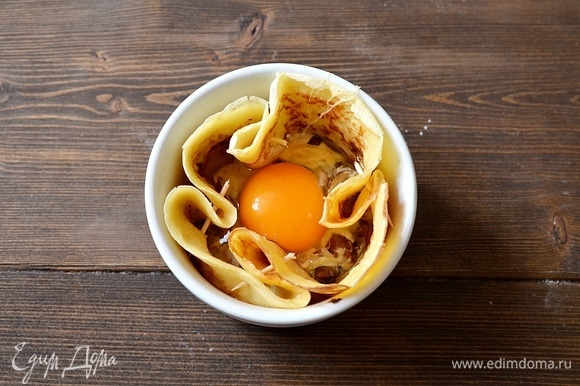 Аккуратно вбейте яйцо. Запекайте в разогретой до 180°C духовке до желаемой консистенции яичницы.