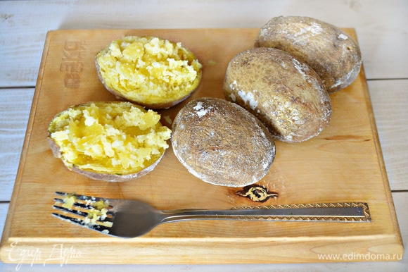 С уже готового картофеля стряхните соль, аккуратно разрежьте картофель пополам, вилкой слегка разомните сердцевину.
