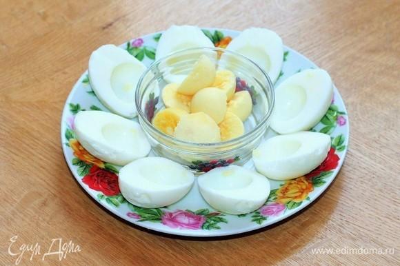 Приготовим начинку для яиц. Яйца отварить, очистить от скорлупы и разрезать каждое на 2 части, вынуть желток.