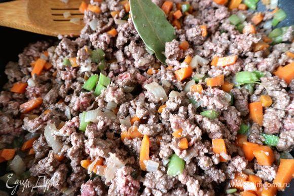 Добавить мясной фарш, соль, перец и лавровый лист, обжаривать мясо, разминая его лопаткой до небольших комочков. Добавить вино, перемешать.