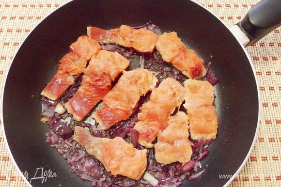 Нарезать филе горбуши совершенно произвольно. Затем обжарить его в сковороде с луком сначала с одной стороны.