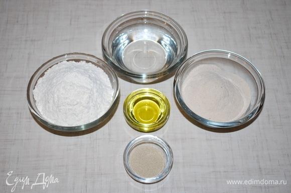 Два вида муки смешайте, насыпьте горкой, в середине сделайте углубление. Влейте в муку разведенные в теплой воде дрожжи, оливковое масло, посолите и заместите тесто.