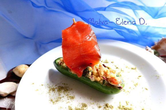 На шпажку или зубочистку поместить кусочек нерки, смазанный оливковым маслом, воткнуть в центр лодочки из огурца «парус». Тарелку посыпала мукой из тыквенных семечек. Приятного аппетита!