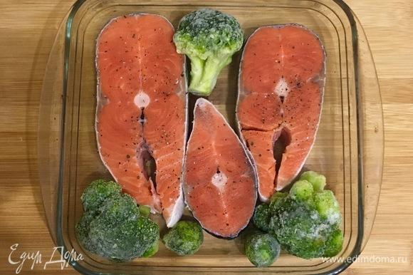 В форму для запекания выложить стейки кижуча и несколько соцветий брокколи. Рыбу посолить и поперчить.