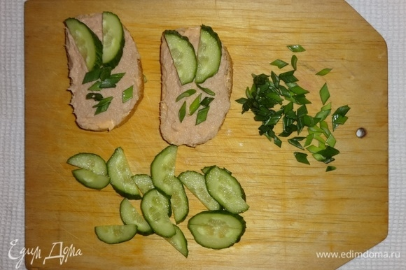 На тосты выложить кусочки огурцов и зеленый лук.