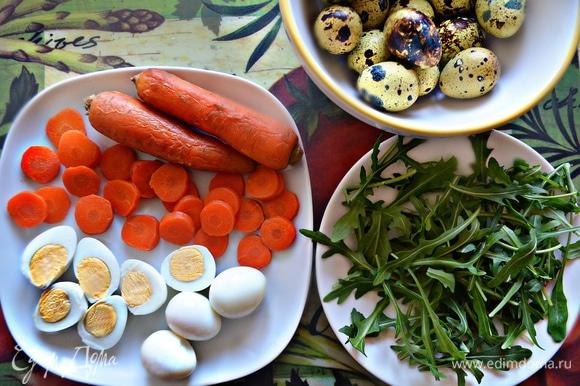 Отварите и почистите перепелиные яйца. Каждое разрежьте пополам. Морковь отварите до готовности, почистите и нарежьте кружочками. Руколу помойте и просушите.