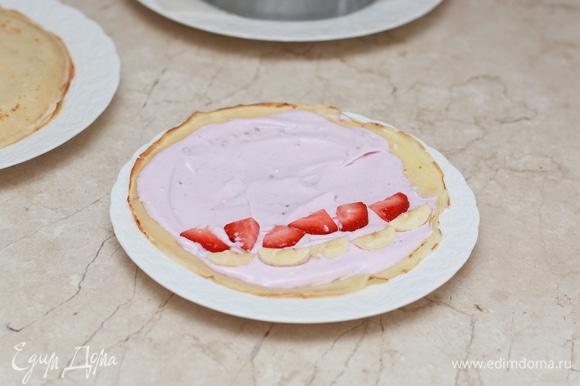 Каждый блинчик смажьте кремом, выложите немного заранее нарезанных фруктов и заверните блинчик в форме рулета.
