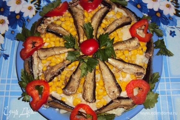 На дно плоской тарелки выложить картофельно-луковую смесь, затем — кукурузу и шпроты (в виде цветка). Оставшиеся шпроты выложить по бокам. Полить салат половиной масла из банки. Украсить кружками красного перца и петрушкой. Подать к столу. Угощайтесь! Приятного аппетита!