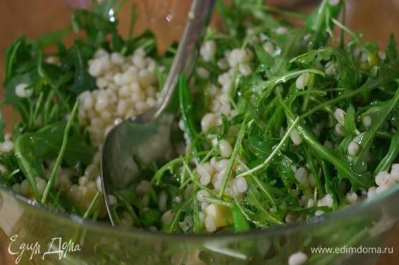 Выложить отваренную перловку в глубокую посуду, добавить руколу, мяту, нарезанный сыр, горох и все перемешать.