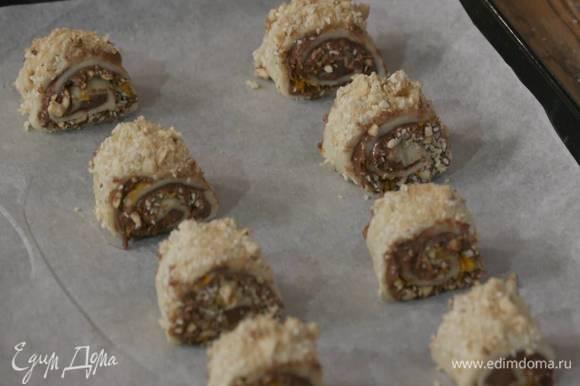 Сверху смазать рулет сливочным маслом, посыпать оставшейся ореховой крошкой и коричневым сахаром, нарезать небольшими кусочками и выложить их на противень, выстеленный бумагой для выпечки.