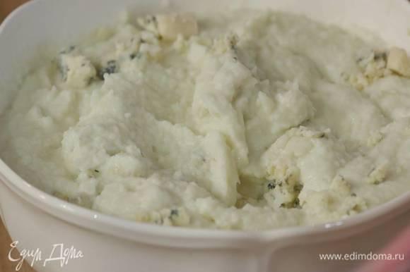 Выложить пюре в глубокую посуду, добавить пармезан и все перемешать, сверху разложить кусочки голубого сыра и слегка вмешать их в пюре.