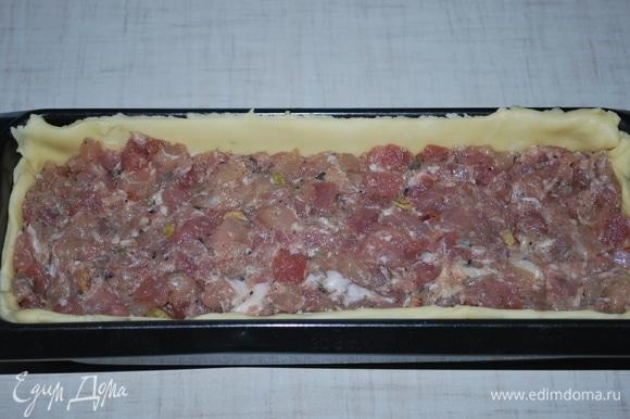 Форму для выпекания смажьте растительным маслом. Раскатайте тесто в пласт, выложите в форму таким образом, чтобы полностью закрыть дно и стенки формы. Форму с тестом заполните начинкой.