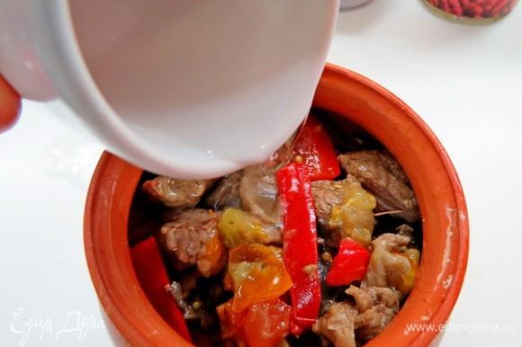 В каждый горшочек налить немного воды (около 50 мл), закрыть горшочки крышкой, томить в разогретой до 180°C духовке в течение часа.