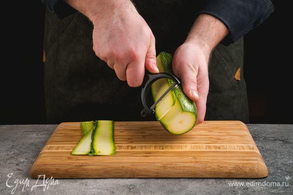 Цукини с помощью овощечистки нарежьте тонкими слайсами.