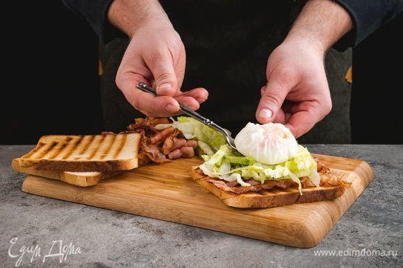 На тосты выложите кусочки бекона, салат айсберг, сверху — яйца пашот и посыпьте тертым сыром.