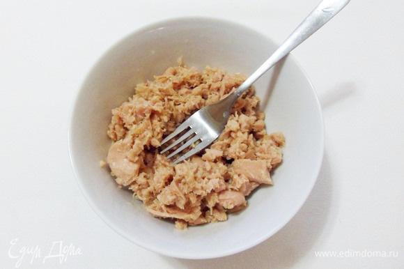Консервированного тунца выложить в миску и размять вилкой.