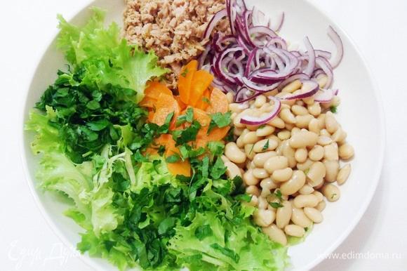 В салатник отправляем листья салата (их можно порвать руками), зелень петрушки, тунца, фасоль, морковь и маринованный красный лук.