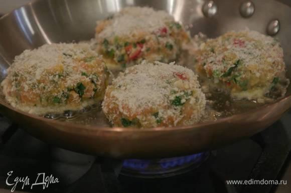 Разогреть в тяжелой сковороде оливковое масло и обжарить котлеты с одной стороны до золотистой корочки, затем перевернуть, накрыть крышкой и жарить еще 3 минуты.